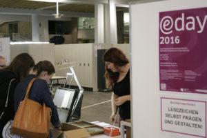 Die Buchbinderinnen der Staatsbibliothek zeigen den BesucherInnen des e-day 2016, wie sie mit Lettern und Prägemaschine Lesezeichen selbst gestalten können
