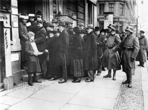 """Wähler in einer Warteschlange vor einem Wahllokal, das von Freikorpssoldaten (""""Landesjäger"""") bewacht wird"""